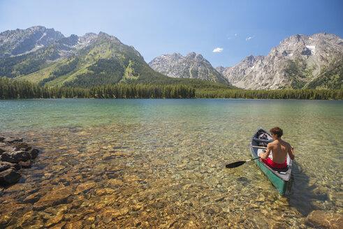 Teenage boy boating in lake against sky - CAVF18303