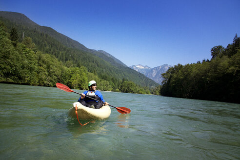 Man looking away while kayaking on river against clear sky - CAVF18348
