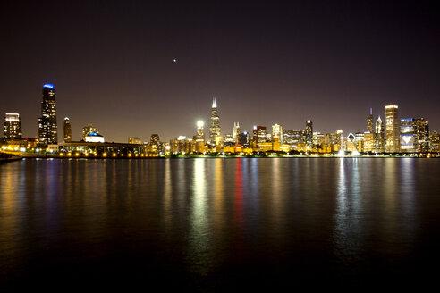 Illuminated cityscape by Lake Michigan at night against sky - CAVF18447