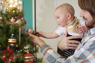 Father showing ornament to baby near Christmas tree at home - CAVF18501