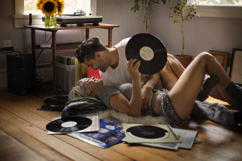 Romantic man lying with woman holding vinyl record on floor at home - CAVF18876