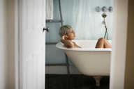Thoughtful woman relaxing in bathtub at home - CAVF18903