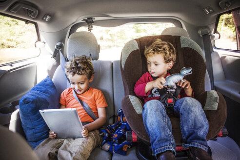 Siblings looking at tablet computer in car - CAVF18927