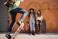 Female friends watching man performing skateboard stunt - CAVF18993