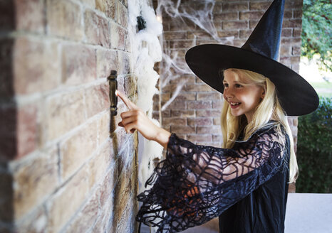 Girl dressed in witch costumes ringing door bell - CAVF19056