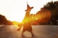 Girl dressed in witch costume walking on road during sunset - CAVF19062