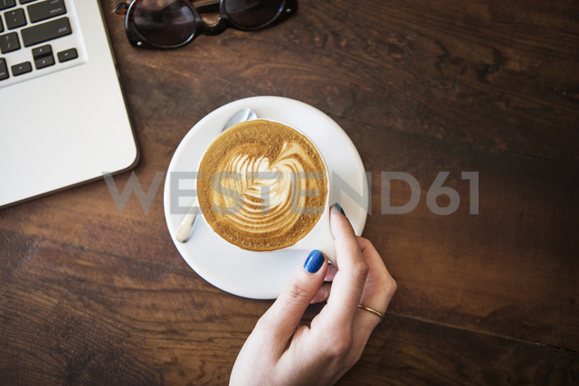 Cropped image of hand with cappuccino on wooden table - CAVF19068