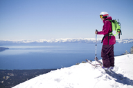 Side view of female skier standing on snowcapped mountain against clear sky - CAVF19287