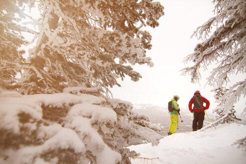 Friends in ski-wear standing on snow field against clear sky - CAVF19401