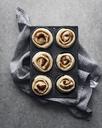 Overhead view of raw cinnamon rolls in baking tray on napkin - CAVF19620