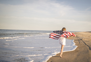 Rear view of teenage girl holding American Flag while running at beach against sky - CAVF19662