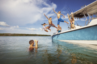 Children jumping from boat at sea against sky - CAVF19716