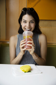 Portrait of happy woman drinking juice and having macaroon at restaurant - CAVF19776