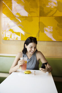 Cheerful woman using phone while having drink at restaurant - CAVF19779