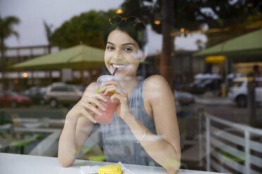 Portrait of cheerful woman drinking juice seen from glass window - CAVF19782