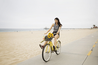 Cheerful woman cycling on street by beach against clear sky - CAVF19794
