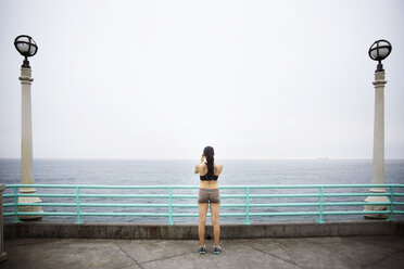 Rear view of woman standing on pier against clear sky - CAVF19809