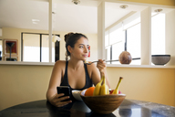 Thoughtful woman eating breakfast on table at home - CAVF19839