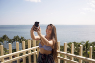 Happy woman clicking selfie against sea on sunny day - CAVF19851