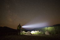 Hiker with illuminated flashlight standing on hill against starry sky - CAVF19902