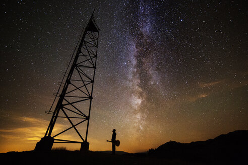 Silhouette man standing by lookout tower against starry sky at night - CAVF19911