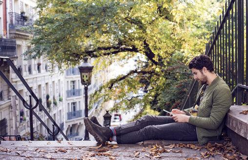 Full length of man using mobile phone while sitting on steps - CAVF19917