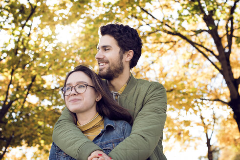 Thoughtful young couple embracing in park during autumn - CAVF19926