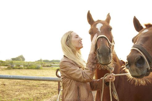 Farmer stroking horse in farm against clear sky - CAVF20082