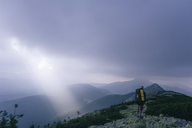 Hiker standing on mountain against cloudy sky during foggy weather - CAVF20136
