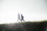 Rear view of male and female friends running on grassy field during sunset - CAVF20208