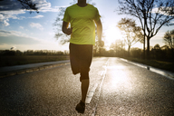 Low section of determined male athlete running on road during sunset - CAVF20226