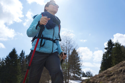 Low angle view of female hiker walking on mountain against sky - CAVF20319