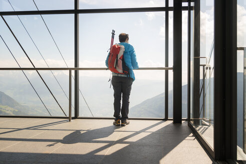 Rear view of female hiker looking at view through glass window at observation point - CAVF20322