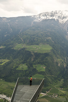 High angle view of hiker standing at observation point against huge mountain - CAVF20325