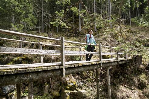 Female hiker standing on footbridge in forest - CAVF20334