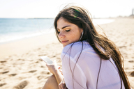 Young woman enjoying music while sitting at beach - CAVF20361