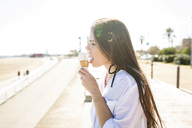 Side view of young woman licking ice cream while standing by beach against clear sky - CAVF20364
