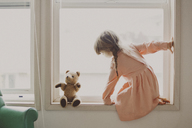 Side view of girl looking at teddy bear while kneeling on window sill at home - CAVF20460
