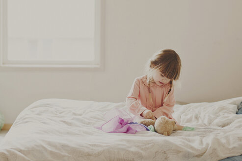 Girl playing with teddy bear on bed - CAVF20463