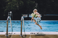 Carefree boy jumping into swimming pool - CAVF20505
