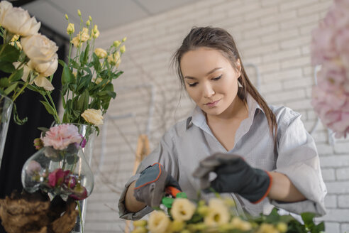 Female florist cutting flower while working in flower shop - CAVF20514