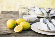 Close-up of lemons by plates on table - CAVF20547
