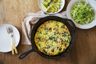 Overhead view of omelet in frying pan on wooden table - CAVF20757