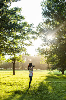 Young woman using retro styled camera while standing on grassy field - CAVF20778