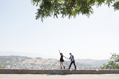 Excited young couple walking on retaining wall against clear sky - CAVF20862