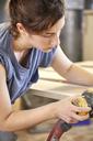 Female carpenter sanding wooden plank in carpentry workshop - CAVF21105