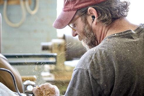 Rear view of craftsperson working in workshop - CAVF21123
