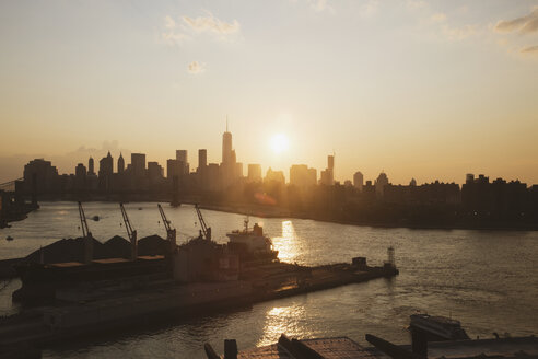 City skyline by river during sunset - CAVF21246