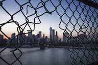 One World Trade Center seen through broken chainlink fence during sunset - CAVF21339