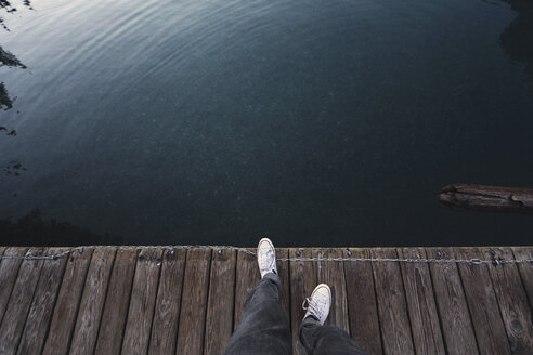 Overhead view of man on boardwalk by lake - CAVF21372